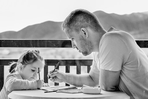 man and child writing at a table